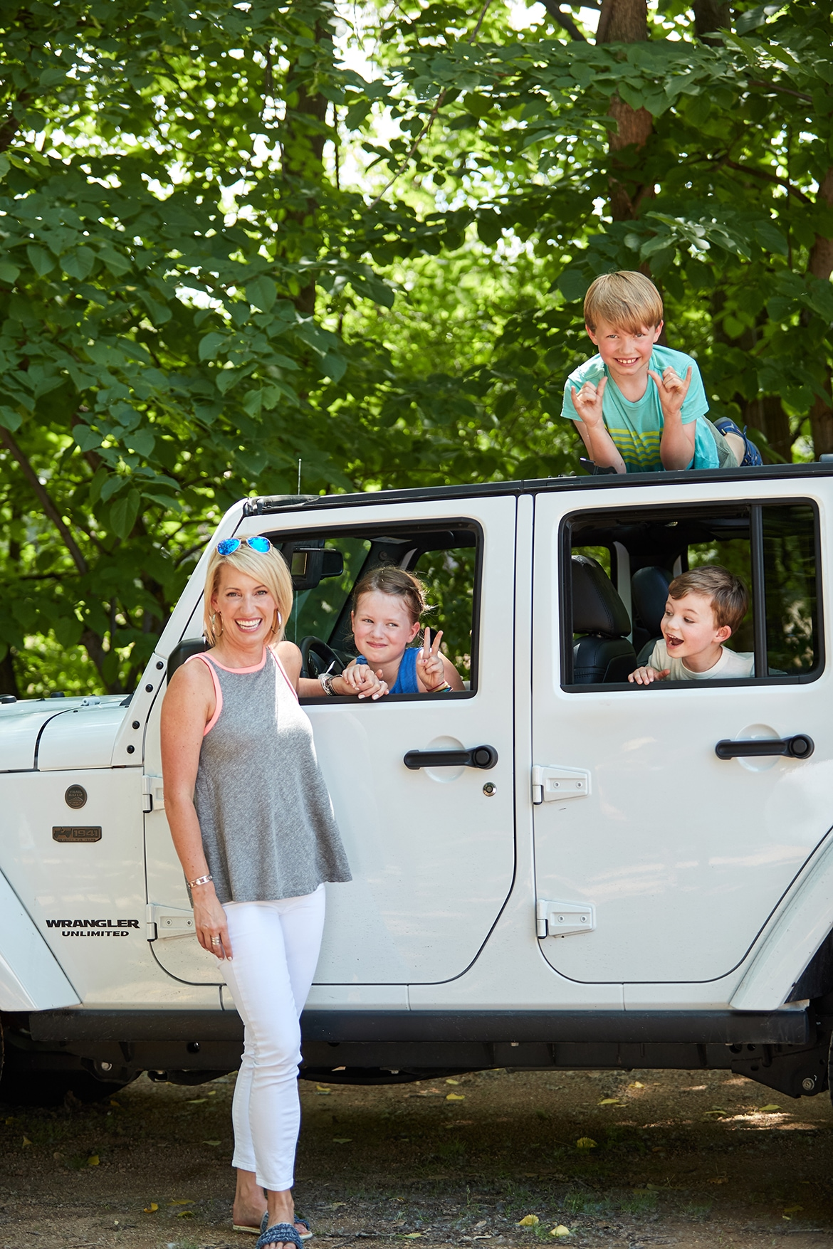 family riding in a white jeep wrangler