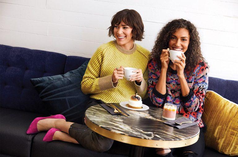 two women wearing sweaters drinking coffee