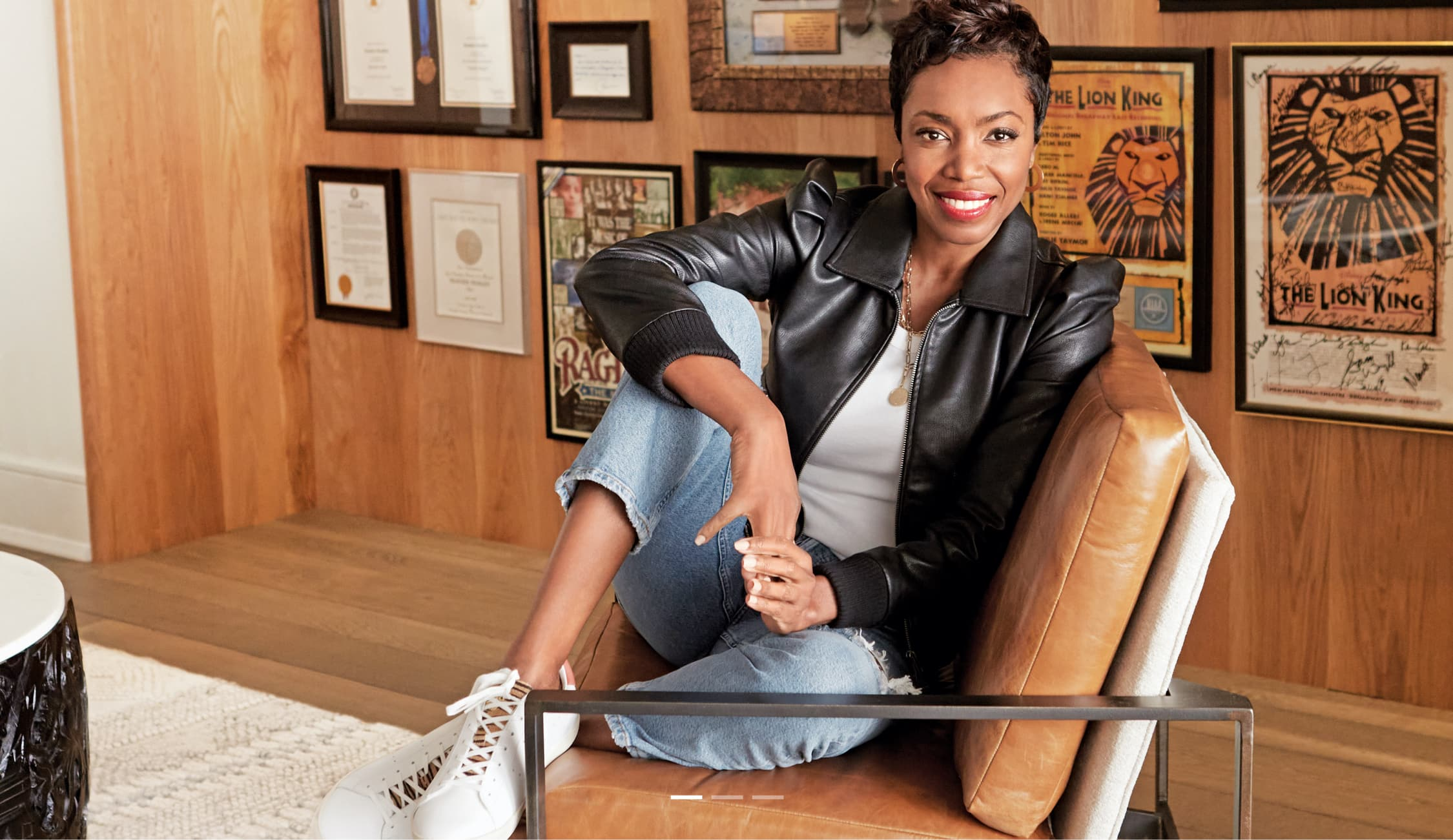 Heather Headley sitting in an armchair and smiling.