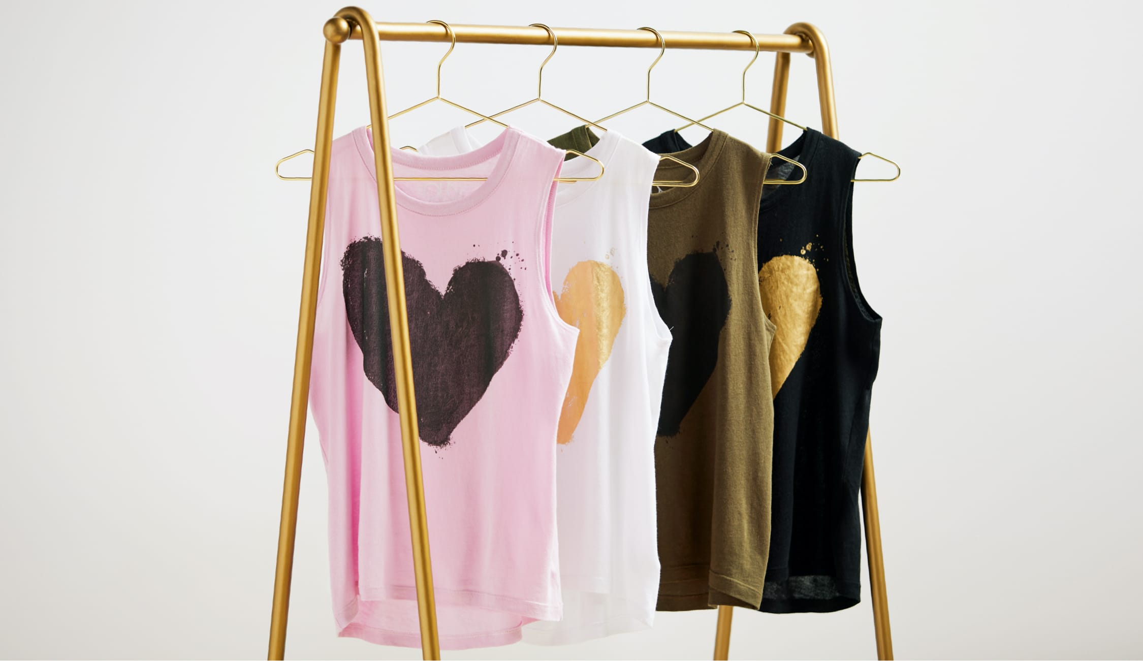 tank tops with heart graphic hanging from a rack