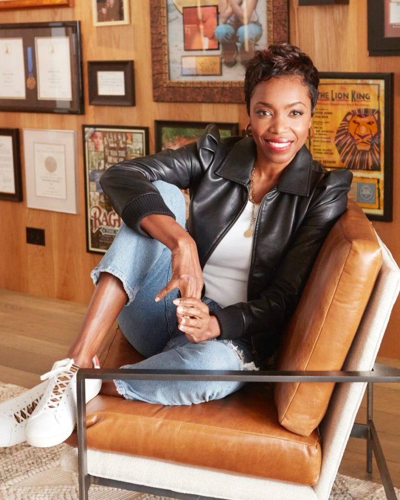 Heather Headley sitting in an arm chair and smiling