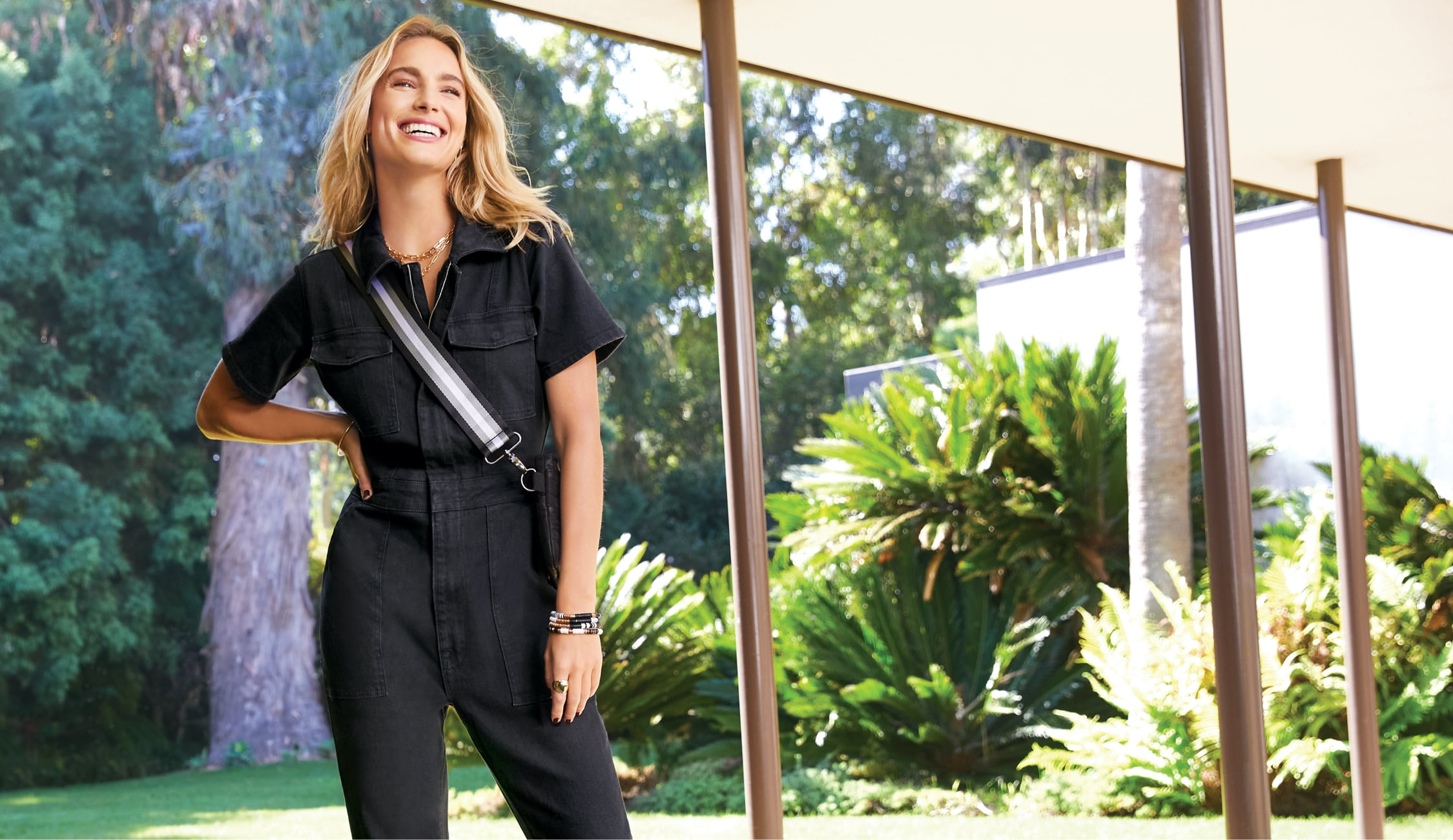 woman wearing a utility jumpsuit and smiling