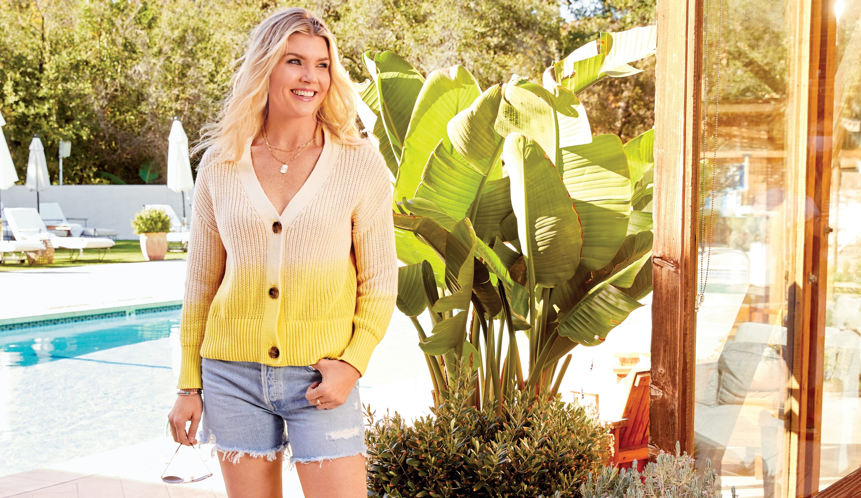 woman wearing a sweater and cutoff jean shorts